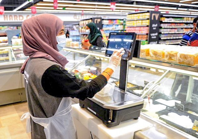 A Saudi female employee serves a customer at a hypermarket, newly launched by the operator LuLu and run by a team of women, in the Saudi Arabian port city of Jeddah, on February 21, 2021. (Photo by Amer HILABI / AFP)
